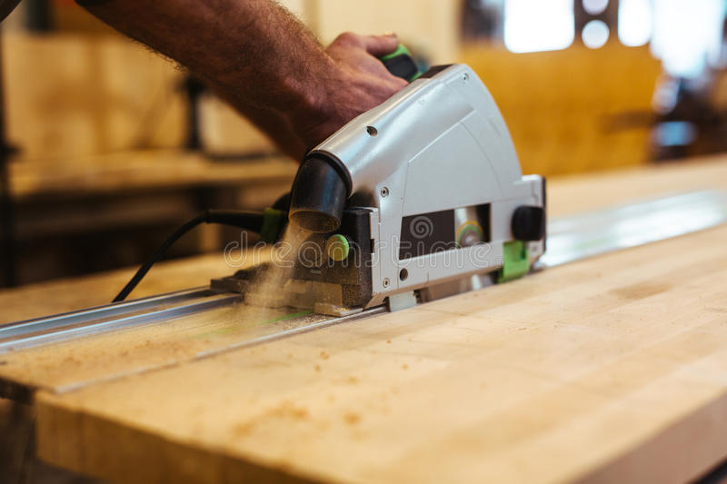 Work with scroll-saw. Human hand with scroll-saw cutting wooden plank royalty free stock photo