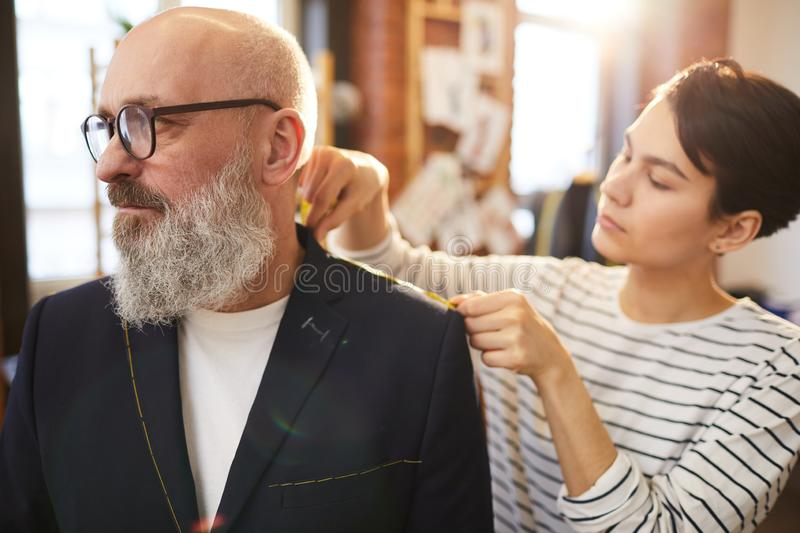 Work of seamstress. Young self-employed seamstress taking measures of unfinished jacket on aged client during fitting in tailoring shop stock photo
