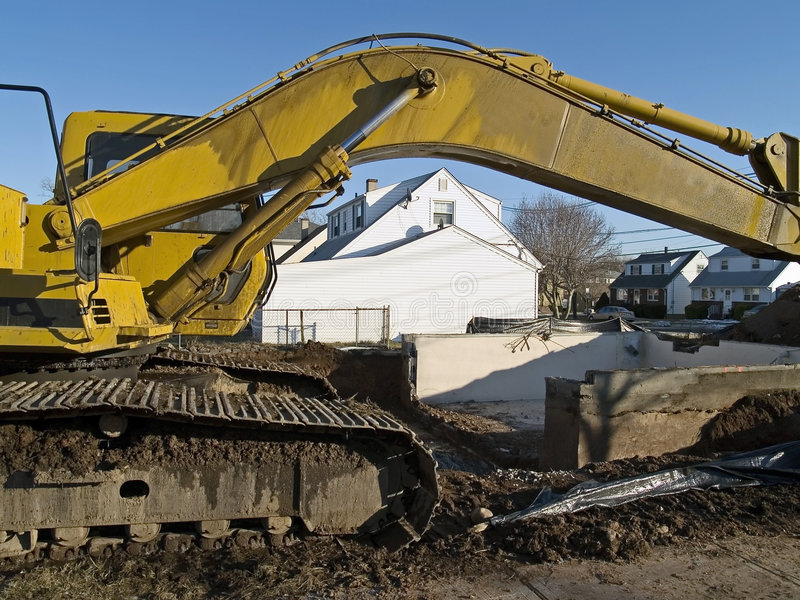 Work Site. A bull dozer frames this work site where a existing home was torn down for new construction stock photos