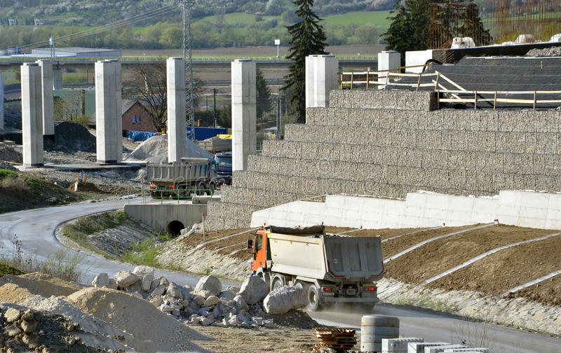 Work site with pillars, sustained wall and trucks driving on the road. stock image