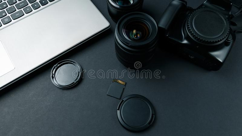 Work space on black table of photographer. Minimal workspace with Laptop, camera and lens copy space on dark background royalty free stock photography