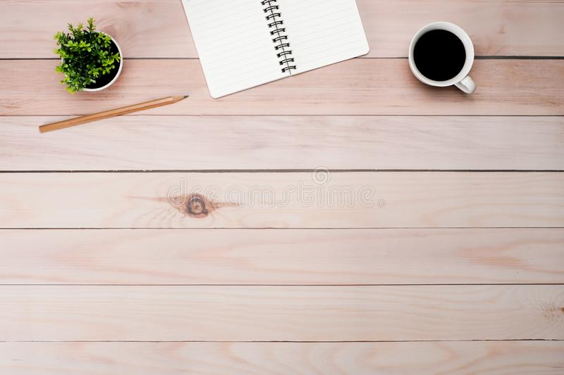Work space brown wooden office table desk with copy space. Work space brown wooden office table desk with blank notepad and coffee cup, leave and supplies, flat royalty free stock photography