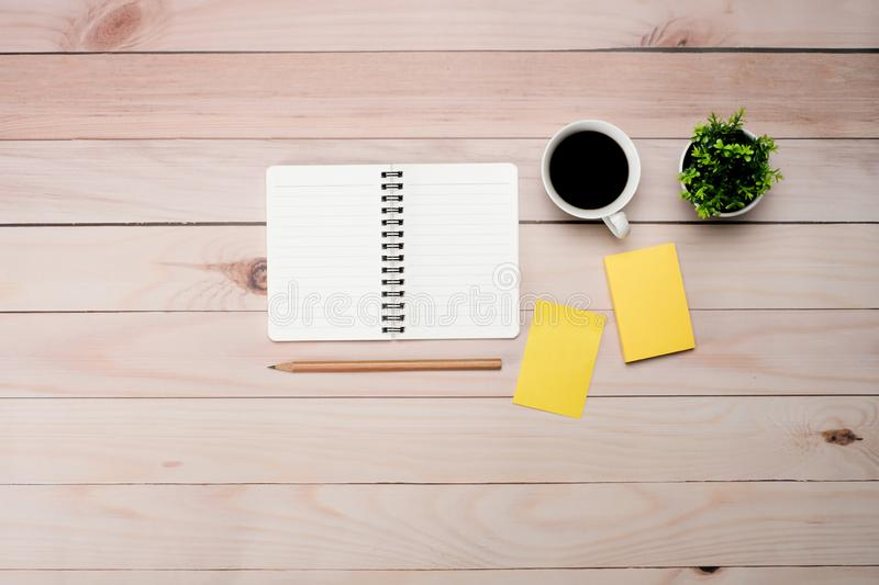 Work space brown wooden office table desk with copy space. Work space brown wooden office table desk with blank notepad and coffee cup, leave and supplies, flat stock images