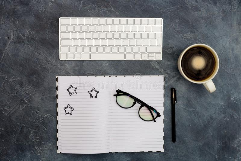 Work space. Office space. Black paper clips and pen on opened blank copybook, coffee, glasses on dark black abstract. Background with copy space, minimal style stock images