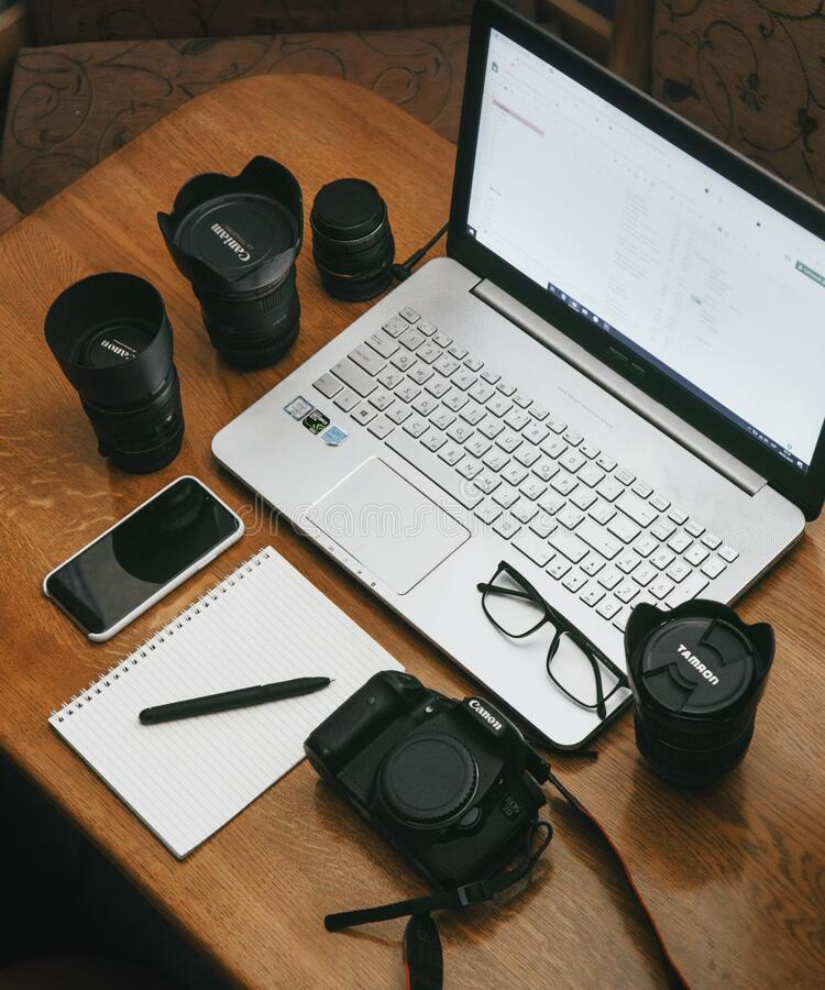 Free Work Space Photographer With Laptop, Digital Camera, Lenses, Notebook, Glasses, Pen, Phone And Camera Accessory. View On Dark Wood Royalty Free Stock Photo - 176886875