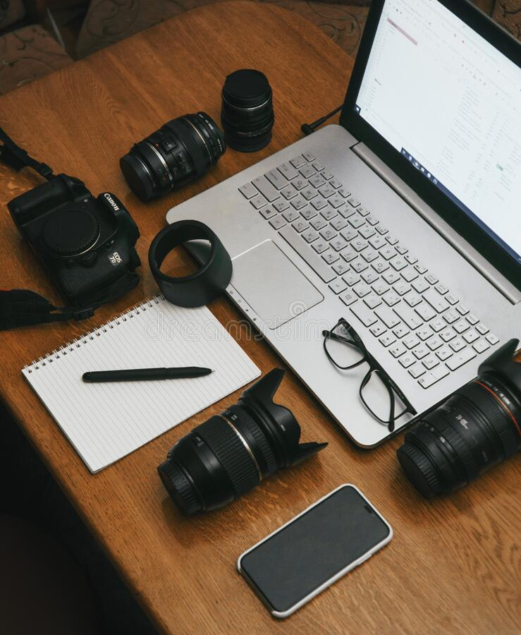 Free Work Space Photographer With Laptop, Digital Camera, Lenses, Notebook, Glasses, Pen, Phone And Camera Accessory. View On Dark Wood Stock Photo - 176886990