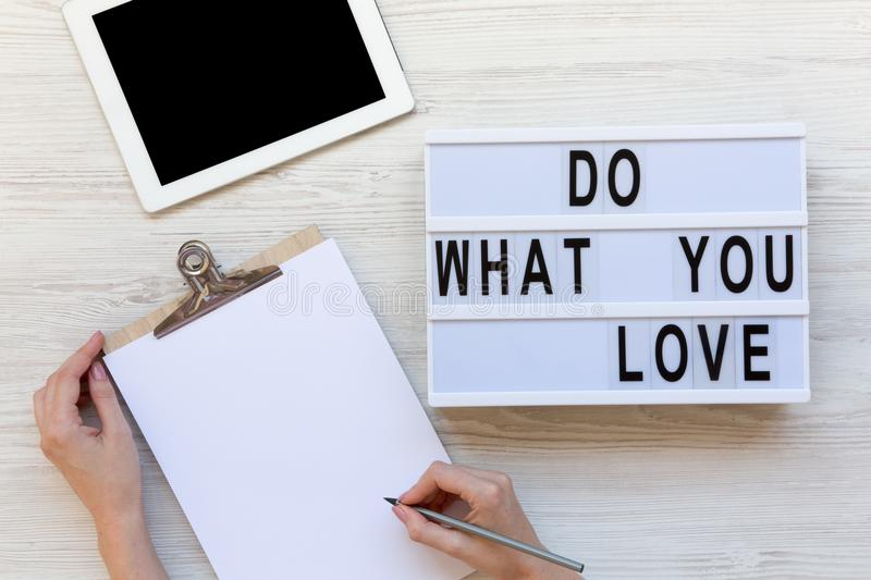 Work space with tablet, female hands, clipboard and `Do what you love` word on modern board over white wooden background, top vi stock images