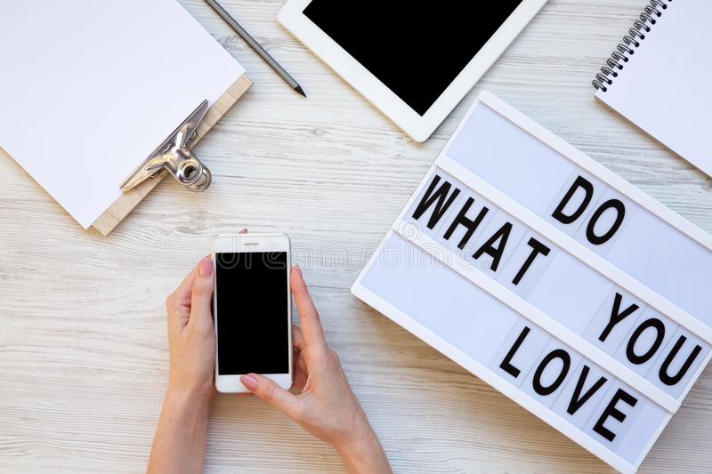 Work space with tablet, female hands, smartphone, clipboard and `Do what you love` word on modern board over white wooden backgr. Ound, top view. From above stock photos