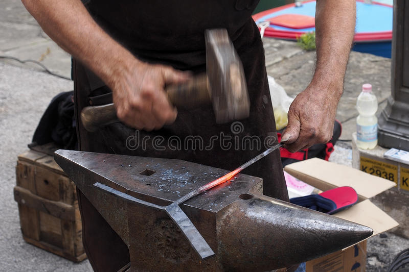 Work. Striking a piece of hot iron. Striking a piece of hot iron on an anvil with the hammer royalty free stock images