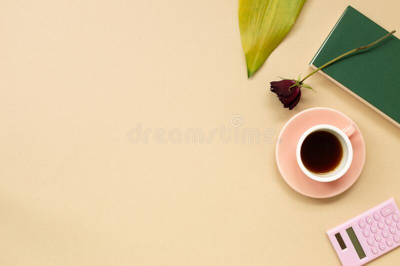 Work and study place. note book, cup of coffee, calculator with floral decoration. Flat lay, top view, copy space stock photos