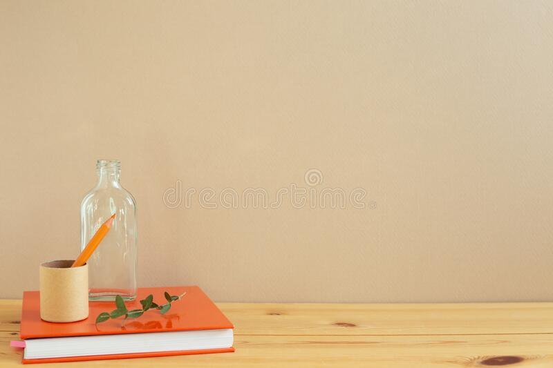 Work and study place. note book, pencil on wooden desk with beige background. Copy space royalty free stock image