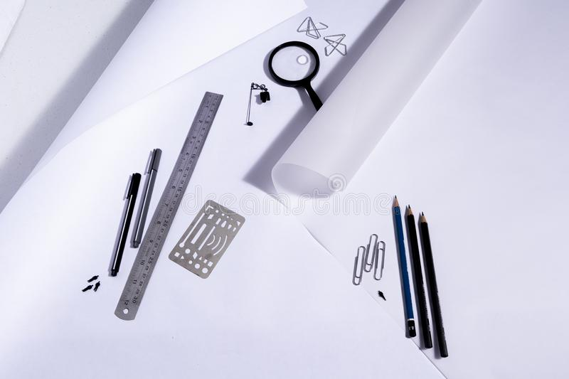 Work table of an architect with blank paper, magnifying glass, ruler, pencils, pens and clips. Architect ready to start work. In b royalty free stock image