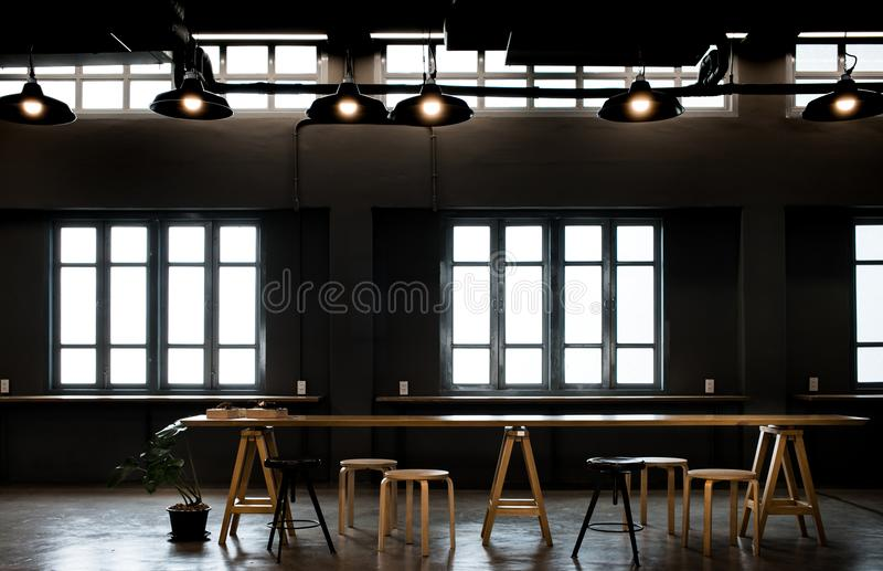 Work table in dark loft cafe design with window stock photo
