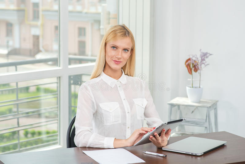 Work on the tablet. Blonde woman works for your tablet and looking at the camera. Young and pretty business woman smiling and loo royalty free stock photos
