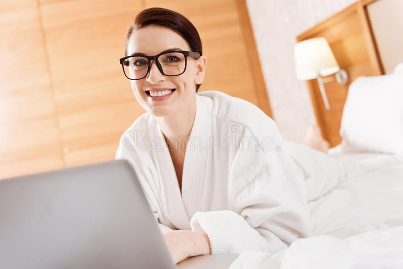 Merry pleasant woman working in the bed stock photos