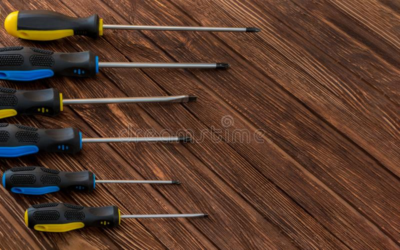 Work tool of the wizard. Different screwdrivers on a wooden surface. Free space for text royalty free stock photo