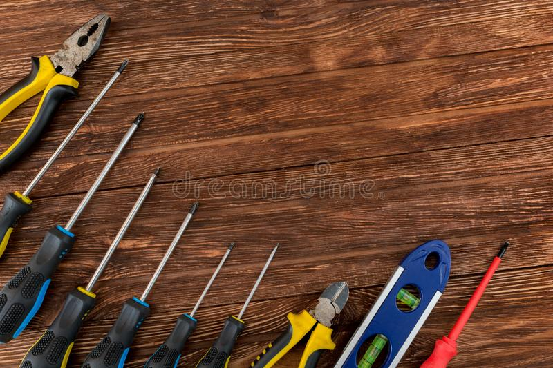 Work tool of the wizard. Screwdrivers, pliers, wire cutters, building level and other tools on a wooden surface. Free space for royalty free stock photos