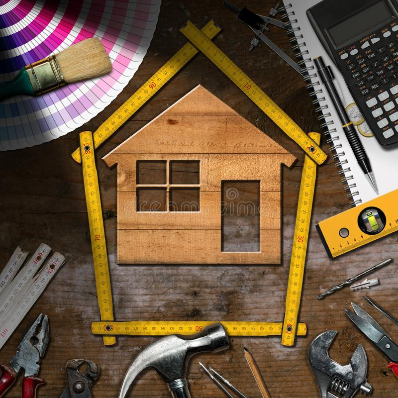Work Tools and Model House - Home Improvement. Home improvement concept - Wooden model house with work tools and a calculator on a wooden desk stock photography
