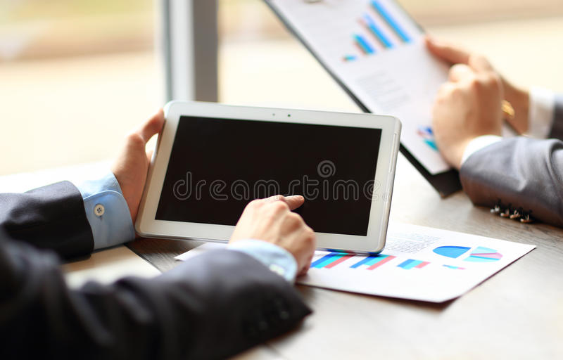 Work of two young businessmen. Using touchpad at meeting royalty free stock photography
