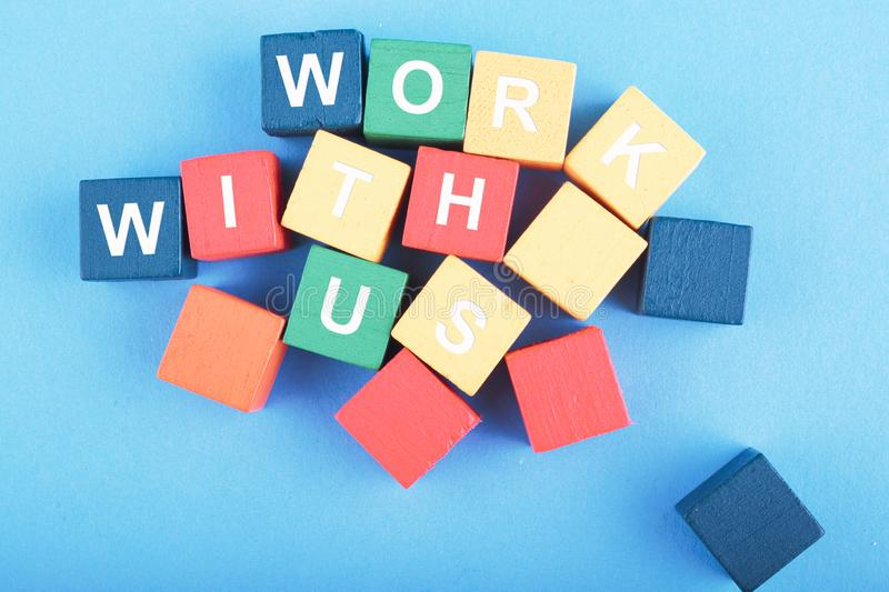 WORK WITH US word on wooden cube over blue background. For recruitment or hiring concept royalty free stock photography