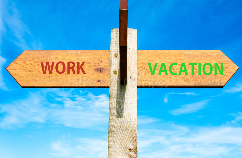 Work and Vacation signs, Work Life Balance conceptual image. Wooden signpost with two opposite arrows over clear blue sky, Work and Vacation signs, Work Life stock photo