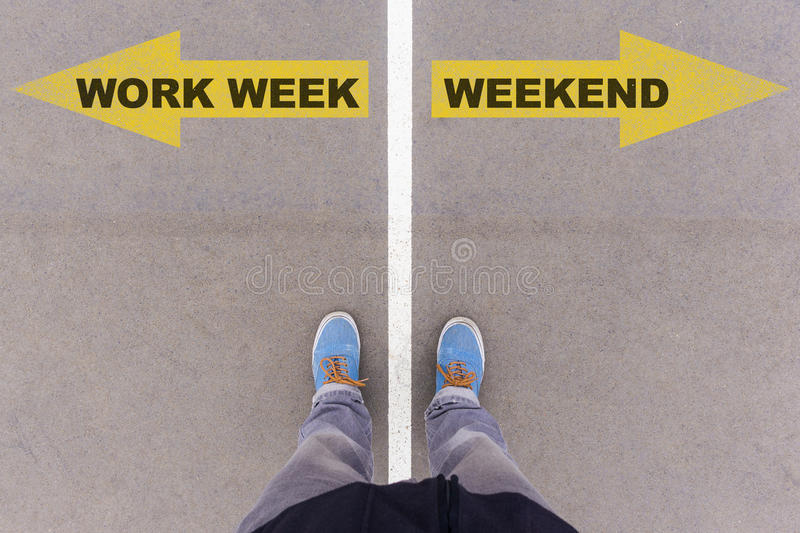 Work week vs weekend text arrows on asphalt ground, feet and shoes on floor. Work Week vs Weekend text on yellow arrows on asphalt ground, feet and shoes on royalty free stock photography