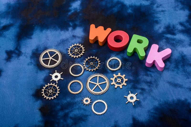 Work wording and wooden cogwheels as industry mechanism. Concept royalty free stock photo