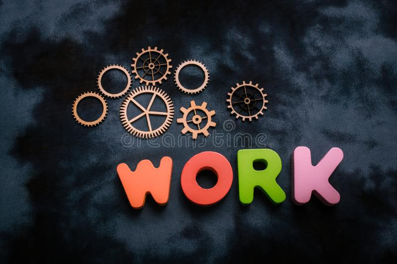 Work wording and wooden cogwheels as industry mechanism. Concept royalty free stock photography