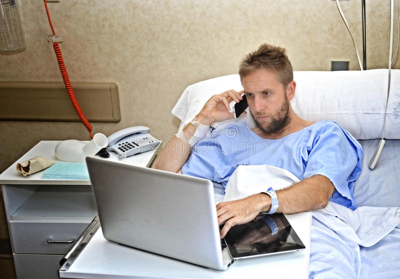 Workaholic business man in hospital room lying in bed sick and injured working with mobile phone computer laptop royalty free stock photography