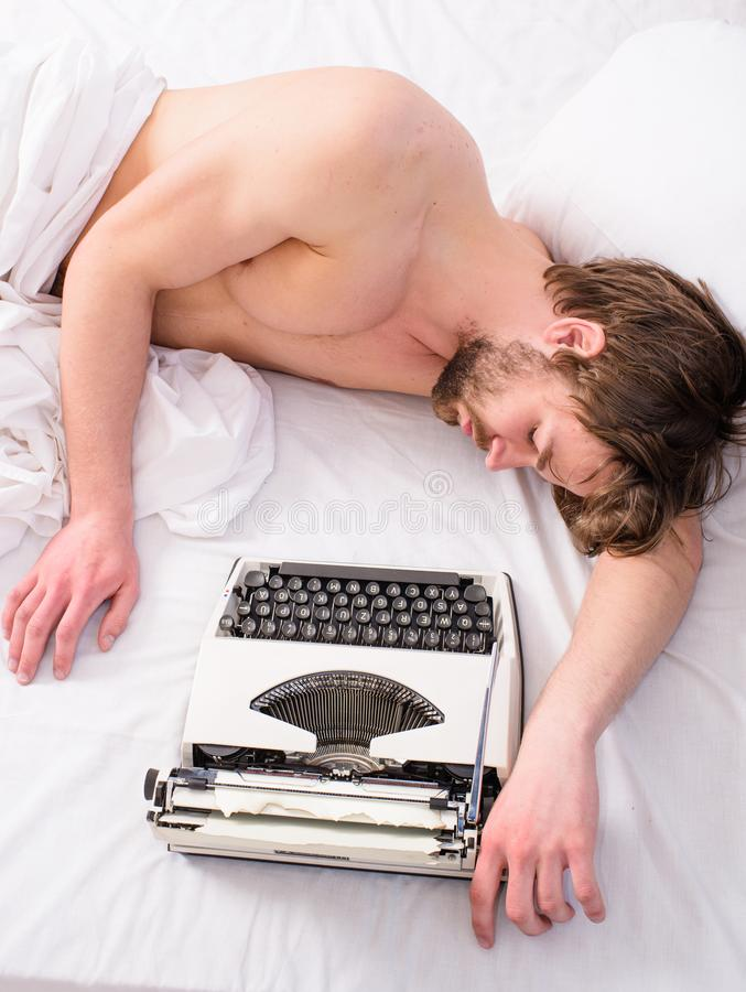 Workaholic concept. Why author use manual typewriter daily work. Man writer sleep bed white bedclothes while worked on. New book. Writer author used old stock photography