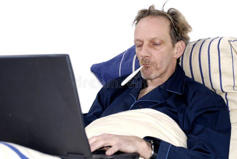 Workaholic, enfermo en cama con la computadora portátil. foto de archivo libre de regalías