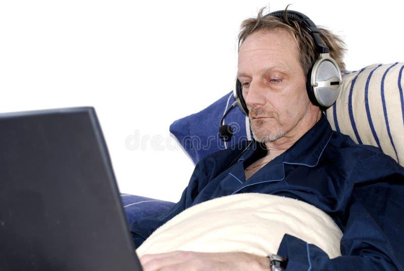 Workaholic, Telefonkonferenz im Bett. stockbild