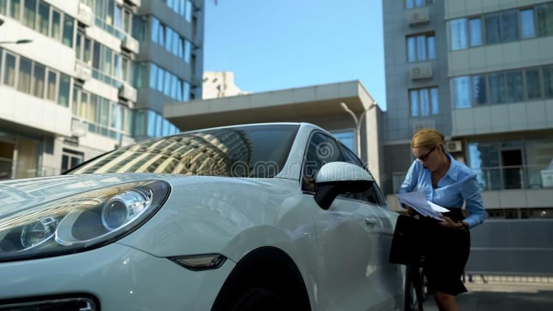Workaholic woman gets out of car, throwing papers, bad day at work absent-minded. Stock photo royalty free stock images