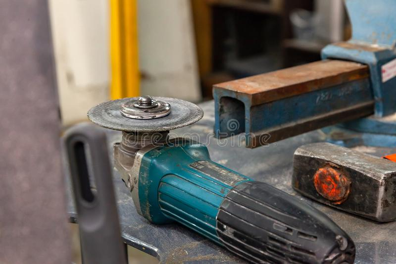 Workbench with a set of tools consisting of a large heavy vise, angle grinder, screwdriver, cutter, sledgehammer, and a spare. Cutting disc in a workshop royalty free stock photos
