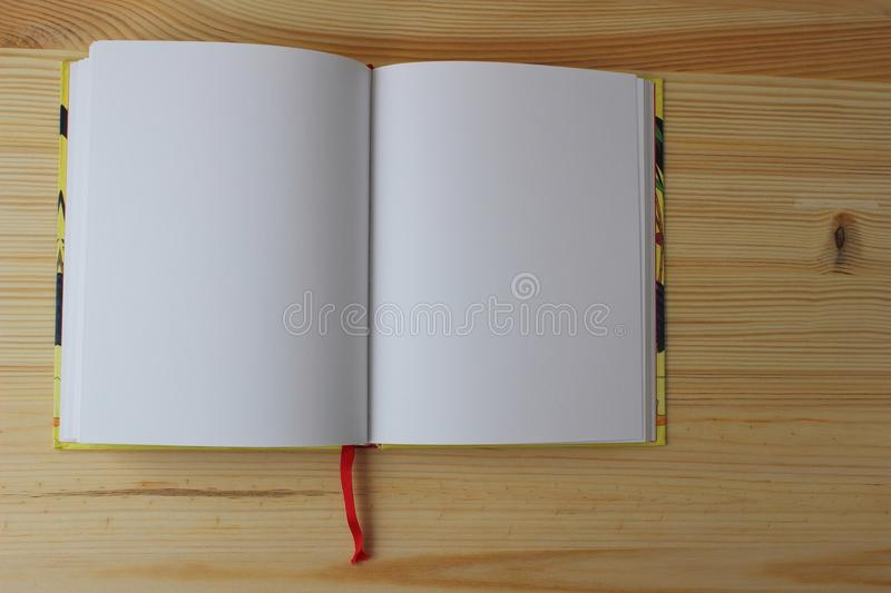 The workbook is open. The open book is on a wooden background left royalty free stock photo