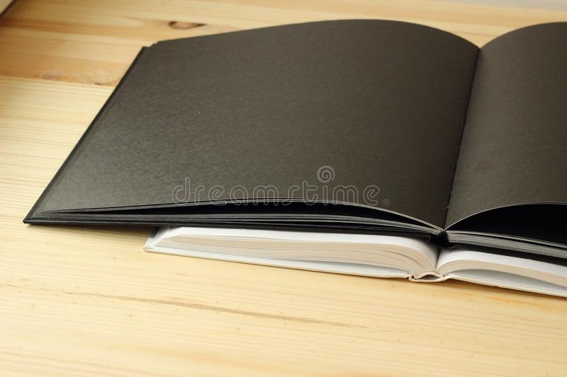 The workbook is open. The open book is on a wooden background, a black notebook lying on white paper royalty free stock images
