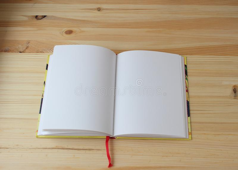 The workbook is open. White open diary is on wooden background center royalty free stock photography