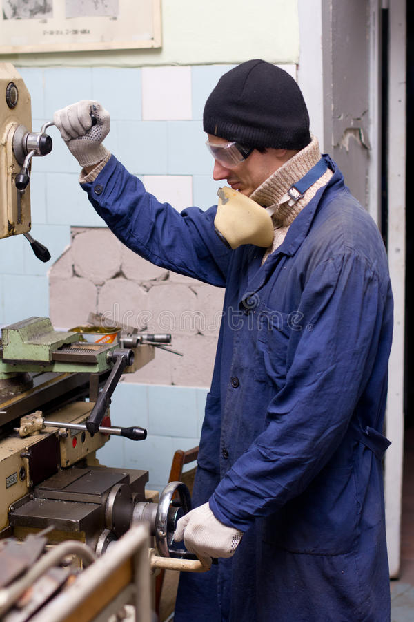 Worker. Mechanical engineer wearing blue boiler suit, protective glasses and gloves working modern milling machine in workshop royalty free stock photos