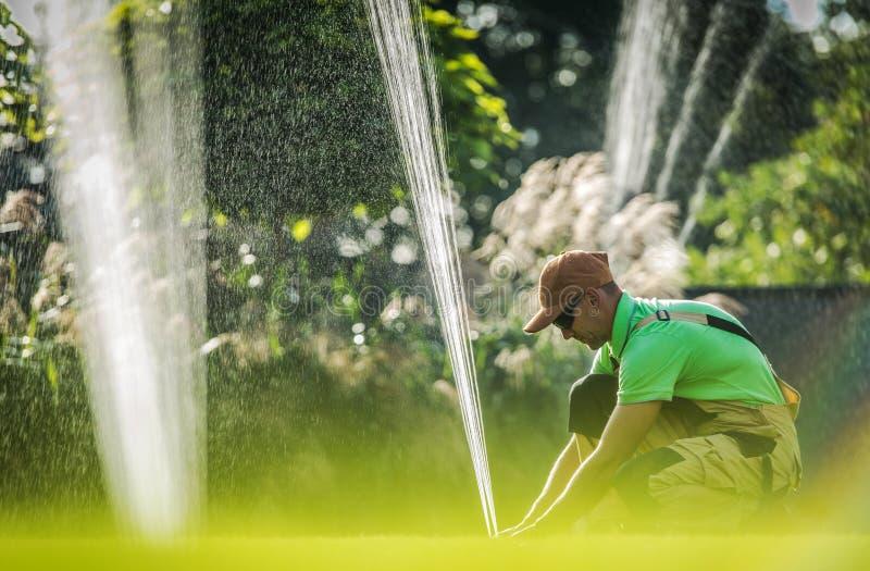 Worker Adjusting Water Sprinkler royalty free stock images