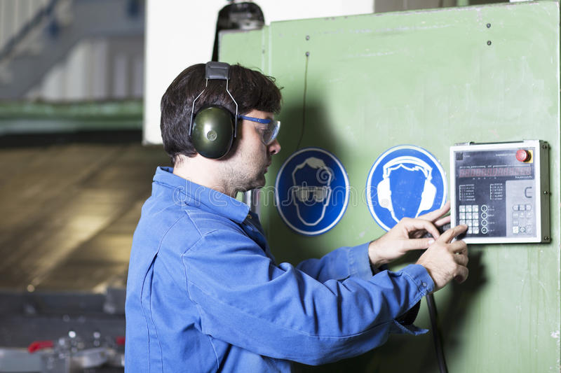 Worker adjusts a machine in factory stock photos
