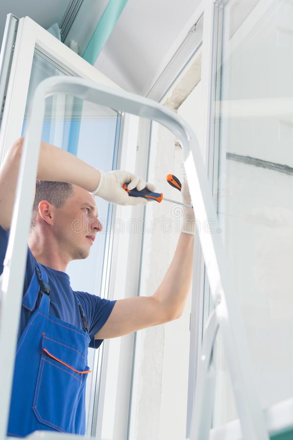 Worker adjusts the plastic window while standing on the stairs royalty free stock photos