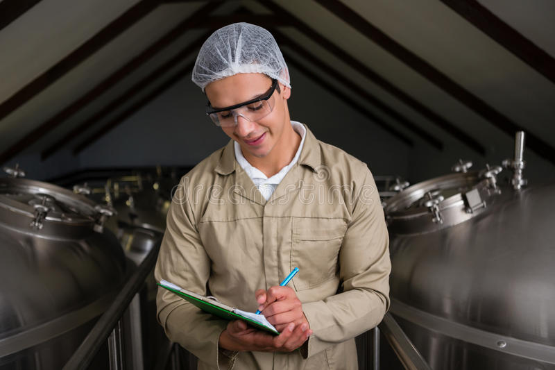 Worker amidst storage tanks writing on clipboard royalty free stock image