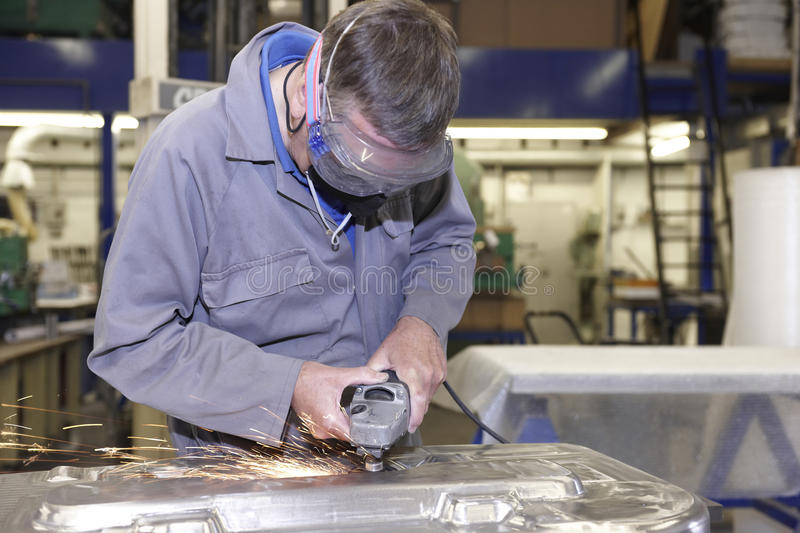 Worker with angle grinder. Factory floor worker using a angle grinder on metal surface stock images