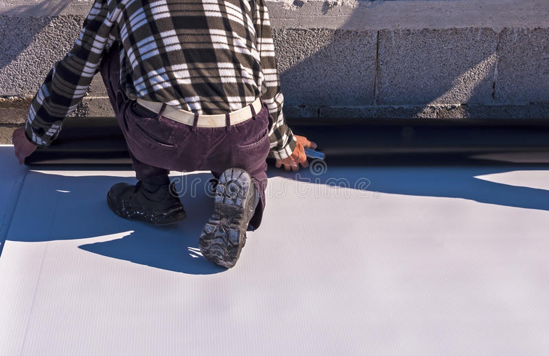 Worker on application Synthetic waterproofing. PVC-P and TPO / FPO stock photos