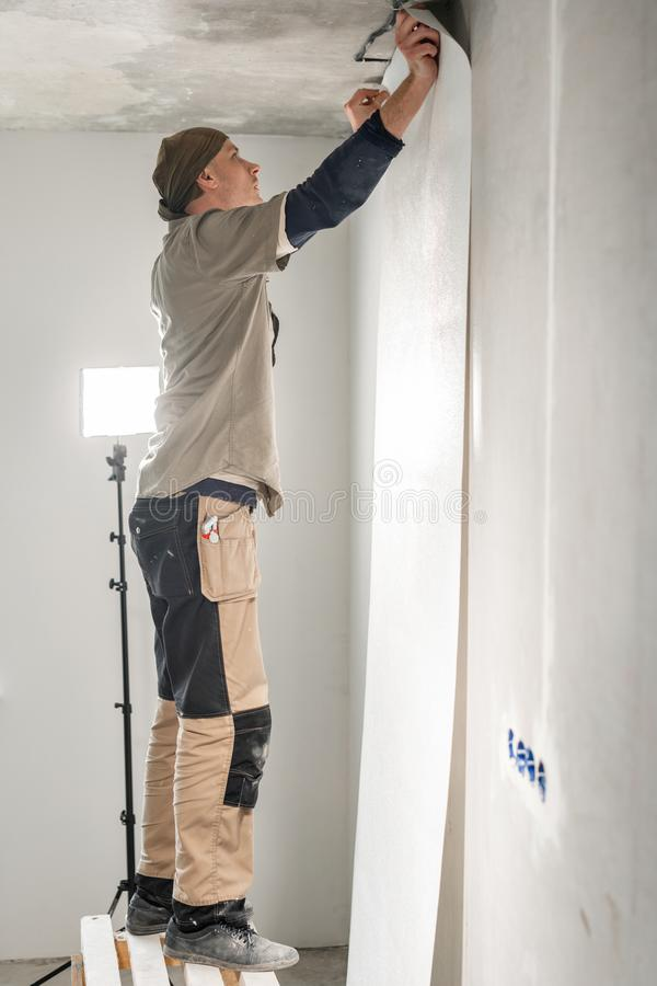 Worker applies a sheet of Wallpaper. Man glueing wallpapers on concrete wall. Repair the apartment. Home renovation stock photo