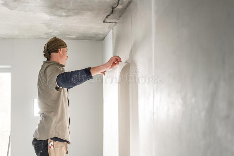 Worker applies a sheet of Wallpaper. Man glueing wallpapers on concrete wall. Repair the apartment. Home renovation royalty free stock photography