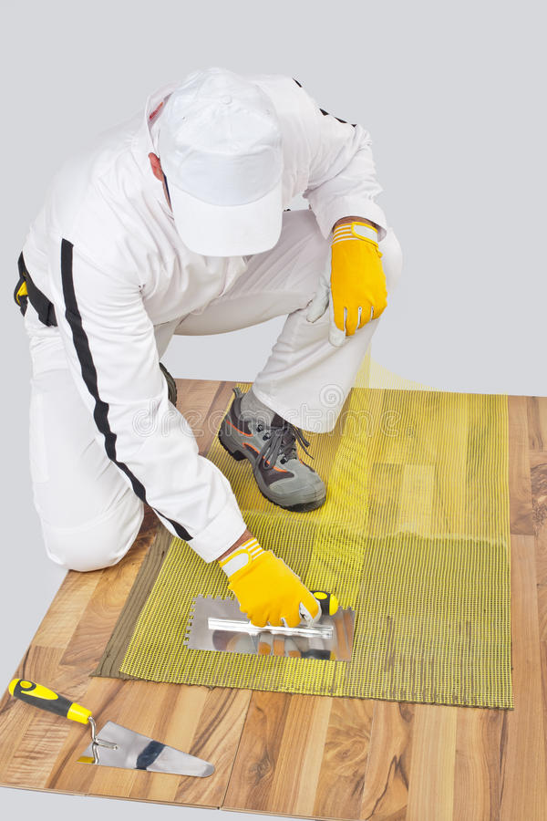 Download Worker Applies Tile Adhesive On Wooden Floor Stock Photo - Image: 25671056