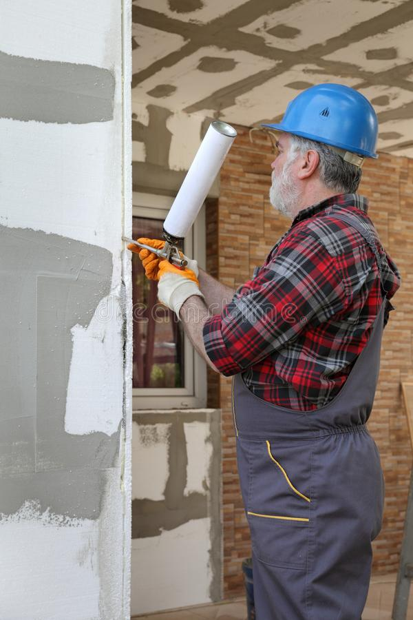 House renovation, polystyrene wall insulation. Worker applying adhesive glue to styrofoam, polystyrene insulation of wall using applicator gun royalty free stock photo