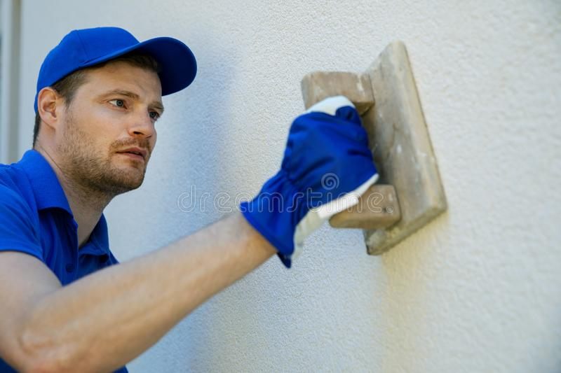 Worker applying decorative facade plaster on house wall royalty free stock photography