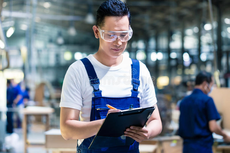 Worker in Asian production plant or factory. Working on checklist with clipboard stock images